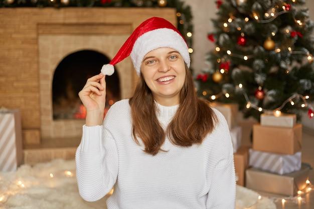 Bella donna in maglione caldo e cappello di natale seduto sul pavimento a casa con scatole regalo, albero di natale e camino, ragazza sorridente felice che tira da parte il suo pom-pom, che celebra il nuovo anno.