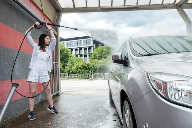 Bella donna che lava e pulisce l'auto con schiuma e acqua a pressione. concetto per la pulizia o la cura dell'auto.