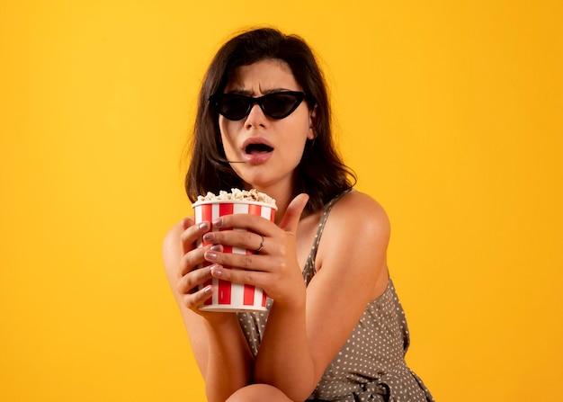 Bella donna che guarda film con popcorn, ha una faccia terrificante