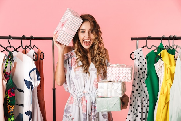Bella donna che indossa un abito in piedi in negozio vicino appendiabiti con scatole presenti isolato sul rosa