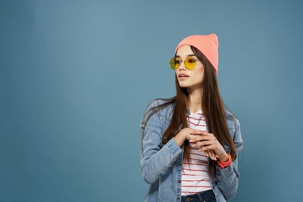 Bella donna che indossa occhiali abbigliamento moderno giacca di jeans sfondo blu