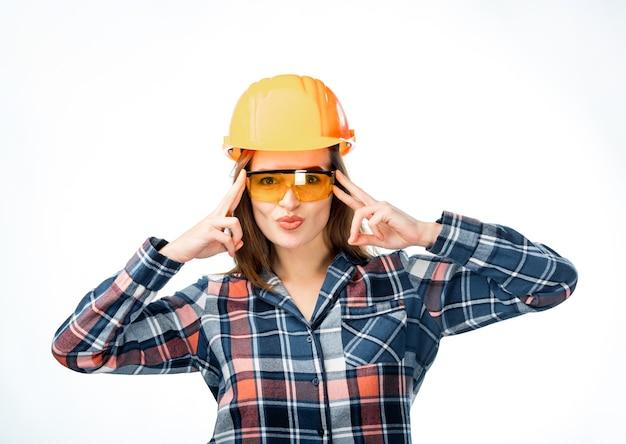 Bella donna che indossa occhiali e casco protettivo arancione. le dita femminili della tenuta si avvicinano alla testa. isolato su sfondo bianco. costruttore femminile in casco di sicurezza