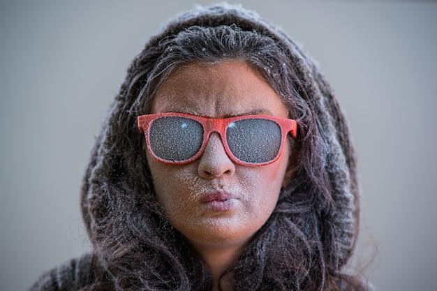 Bella donna che indossa l'abito invernale e occhiali da sole