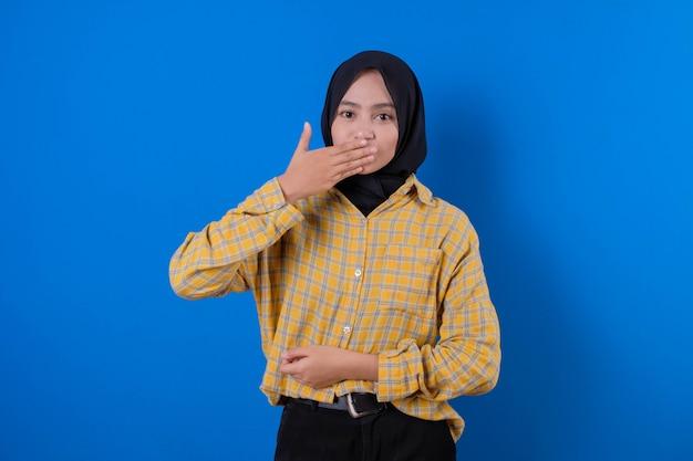 Bella donna che indossa gonna gialla e sorriso gesticolando chiudere la bocca con le mani