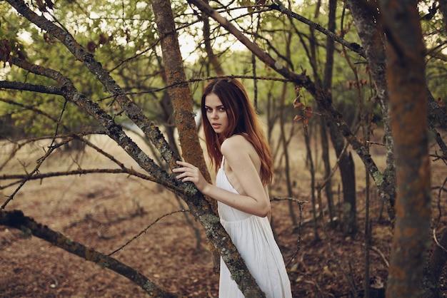 Bella donna in abito bianco appoggiata a una passeggiata estiva sull'albero