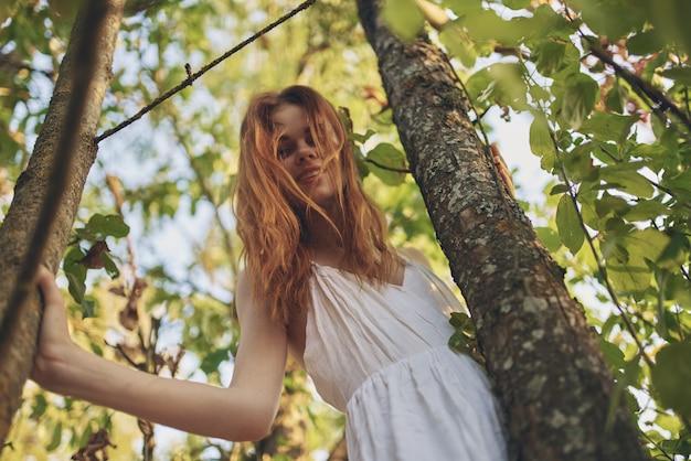 Bella donna in abito bianco natura foglie verdi di un albero vista dal basso. foto di alta qualità