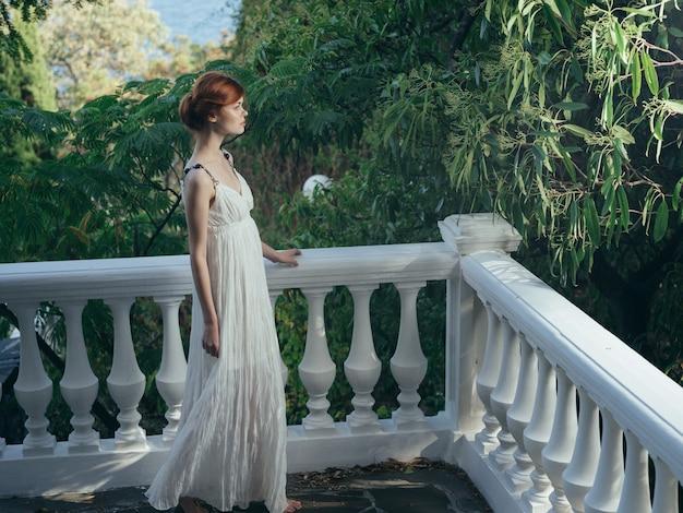 Bella donna in abito bianco nella principessa della decorazione del parco in grecia