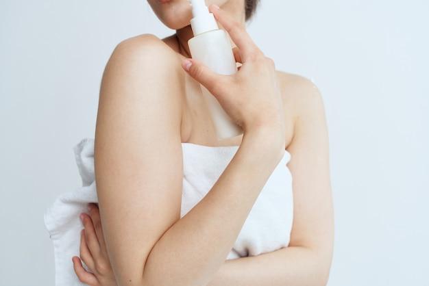 Bella donna in asciugamano bianco spalle nude lozione igiene della pelle pulita