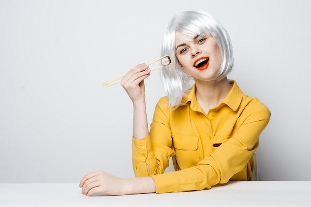 Bella donna in parrucca bianca che mangia sushi rotoli ristorante