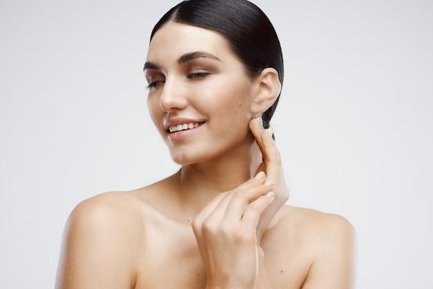Bella donna con le spalle nude e cosmetici per il primo piano della pelle pulita