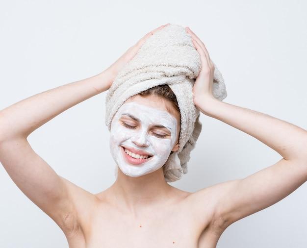 Bella donna con le spalle nude crema per il viso asciugamano sulla pelle pulita testa.