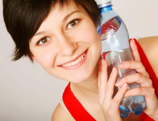 Bella donna con una bottiglia di acqua pulita