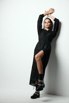 Bella donna con trucco luminoso in un abito nero si è appoggiata al muro con le braccia sopra la testa