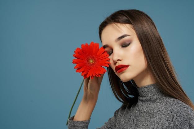 Donna graziosa con lo studio glamour del regalo del fiore rosso di trucco luminoso