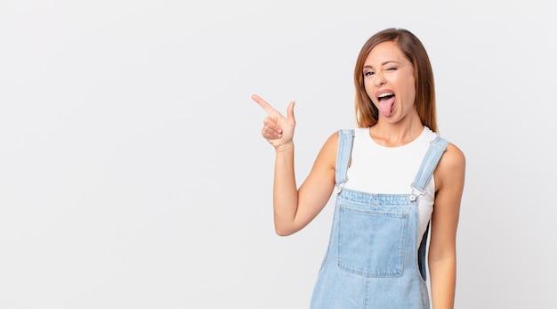 Bella donna con un atteggiamento allegro e ribelle, scherzando e tirando fuori la lingua e uno spazio di copia a lato