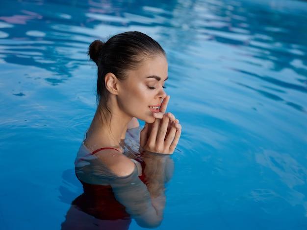 Bella donna con gli occhi chiusi in costume da bagno rosso in piscina di lusso