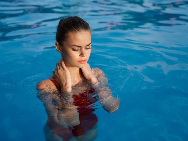 Bella donna con gli occhi chiusi in costume da bagno in piscina all'aria fresca rilassante