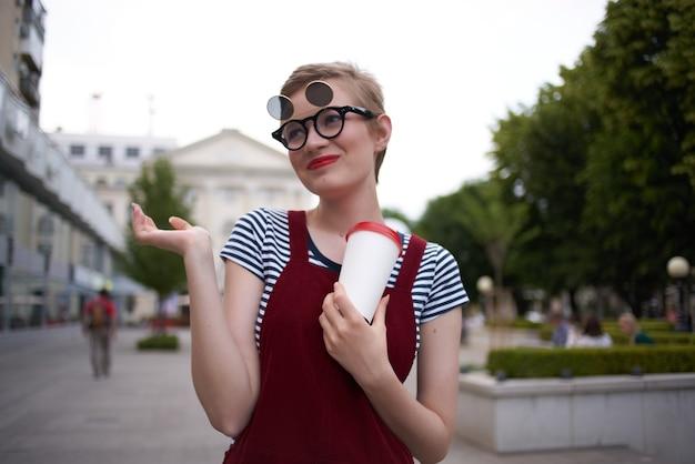 Bella donna con gli occhiali all'aperto che cammina con il caffè nelle mani