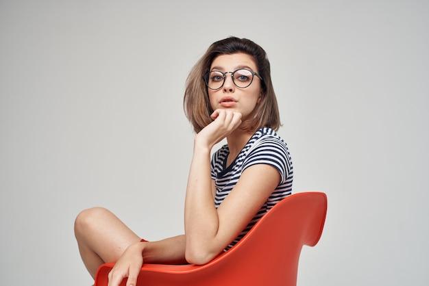 Bella donna con gli occhiali seduta sullo stile di vita di sfondo chiaro della sedia rossa