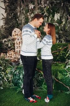 Bella donna con il marito si tengono per mano l'un l'altro con diverse decorazioni natalizie