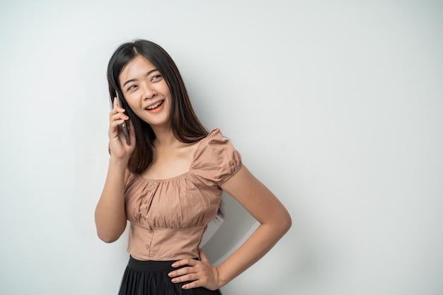 Donna graziosa con il sorriso di capelli lunghi quando si chiama utilizzando lo smartphone