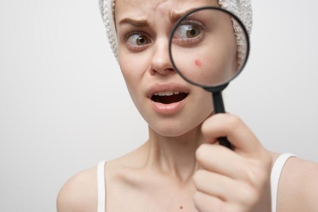 Bella donna con una lente di ingrandimento in mano cosmetologia studio. foto di alta qualità