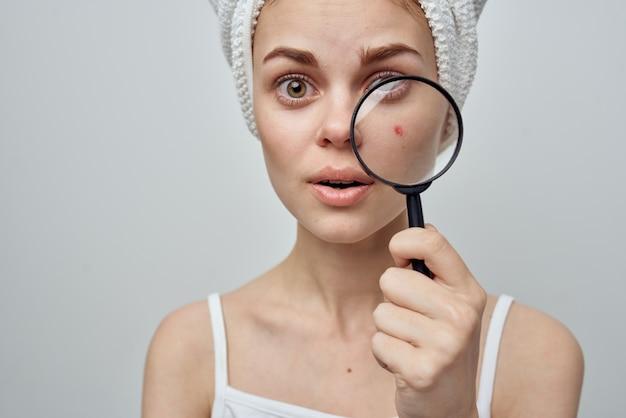 Bella donna con una lente d'ingrandimento in mano studio di cosmetologia