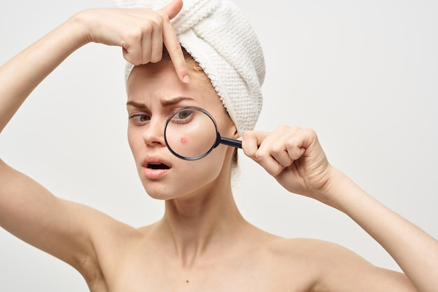Bella donna con una lente d'ingrandimento in mano dermatologia isolato sfondo