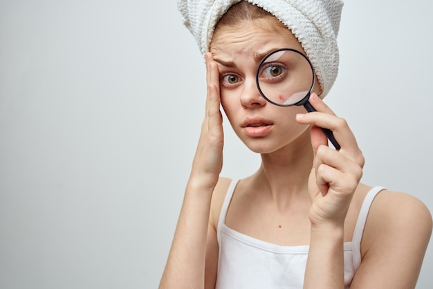 Bella donna con una lente d'ingrandimento in mano problemi di pelle primo piano