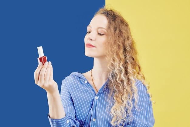 Bella donna con la bottiglia di smalto per unghie