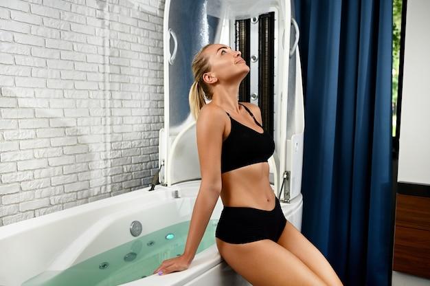 Bella donna con una pelle perfetta che si prepara per il trattamento di bellezza spa in capsula spa. idro e vibromassaggio in un moderno centro benessere