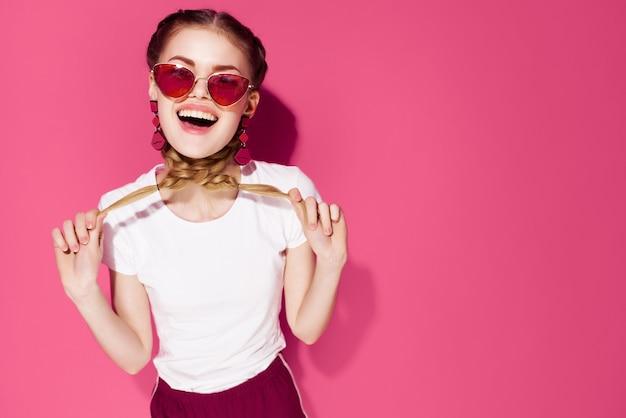 Bella donna con le trecce che indossa occhiali da sole sfondo rosa street style