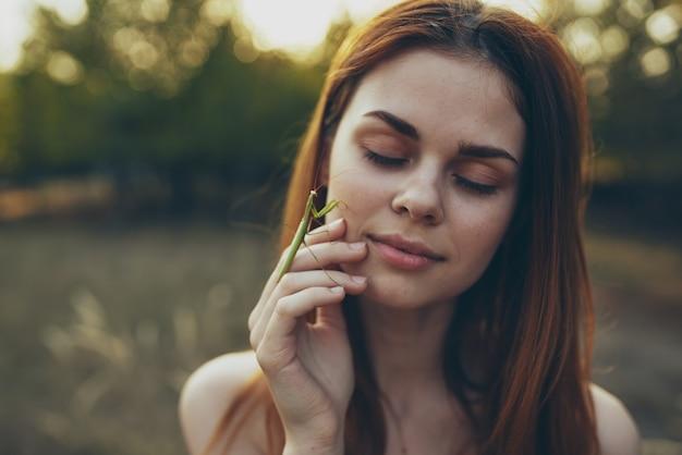 Bella donna con una mantide religiosa in mano natura selvaggia