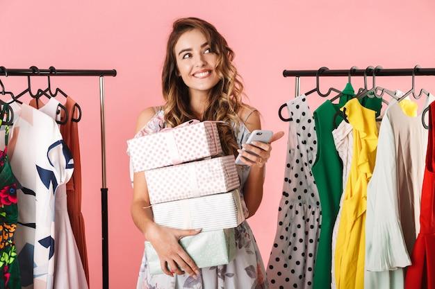 Bella donna con acquisto in piedi in negozio vicino a stendibiancheria e utilizzando il telefono cellulare isolato in rosa