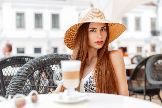 Bella donna con labbra rosse in un elegante cappello seduto in un caffè estivo
