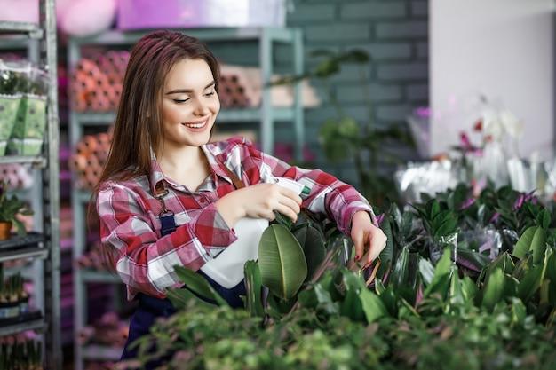 Bella donna con flacone spray che spruzza piante