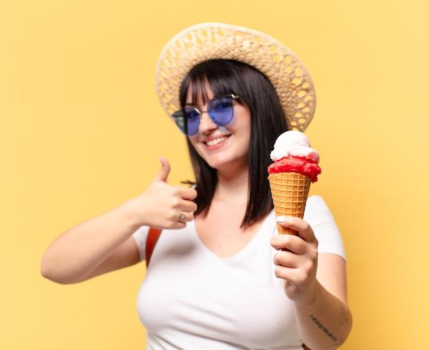 Bella donna con occhiali da sole, gelato e un cappello in vacanza