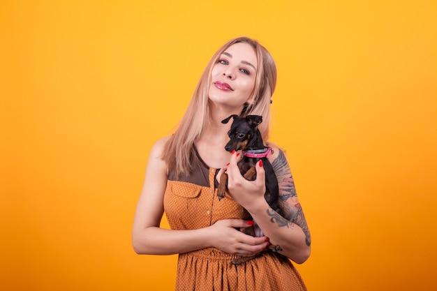 Bella donna con un tatuaggio sul braccio che tiene il suo cagnolino carino su sfondo giallo. bel vestito. donna attraente. amore di cucciolo.