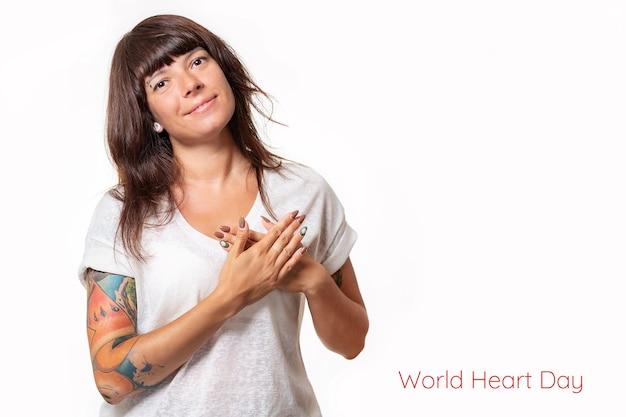 Una bella donna con tatuaggi sul braccio tiene il suo cuore con le mani e sorride. sfondo bianco. copia spazio. il concetto di giornata mondiale del cuore.