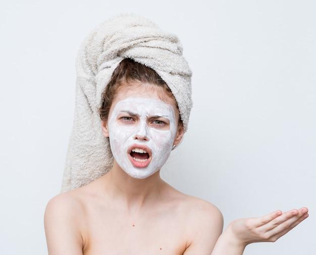 Bella donna con un asciugamano sulla sua testa viso maschera spalle nude sguardo attraente.
