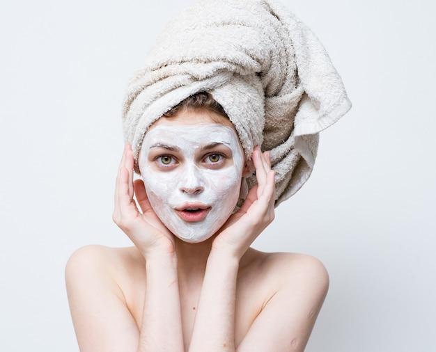 Bella donna con un asciugamano in testa e una maschera bianca contro i punti neri sul viso.