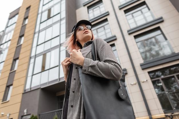 Una bella donna con occhiali vintage e un cappello con una camicia a quadri alla moda con una borsetta cammina vicino a un edificio in città