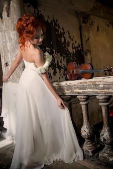 Bella donna con violino. violinista e attrice. la ragazza con un'immagine e un abito da palcoscenico, un costume in una vecchia stanza strutturata tiene o suona il violino. concetto di poster musicale. spazio dell'autore in foto