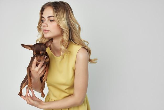 Una bella donna con un vestito giallo si diverte con un cagnolino tagliata alla moda