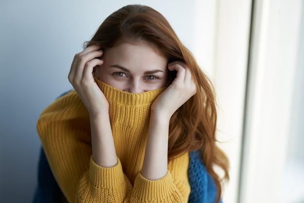 Pretty woman in maglione giallo sorriso sguardo attraente home interior
