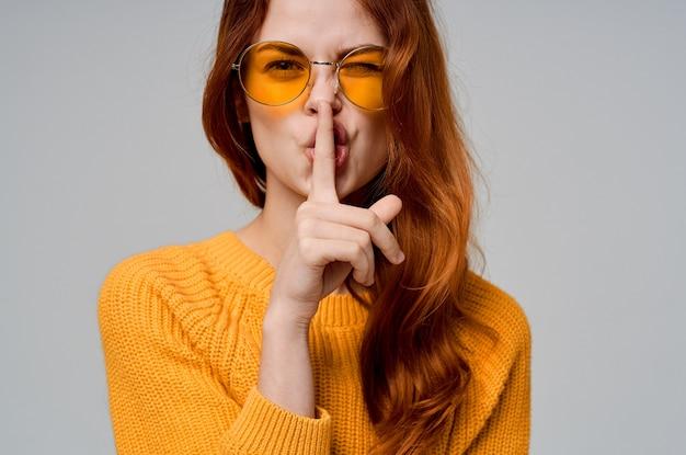 Bella donna in maglione giallo con occhiali moda studio