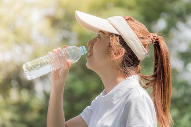 Atleti donne graziose bevono acqua dalle bottiglie di plastica
