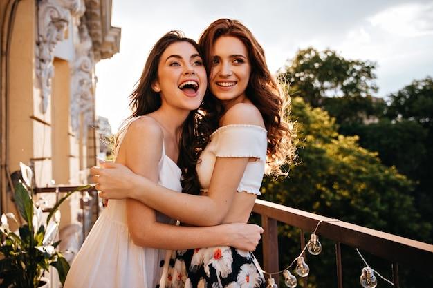 Belle donne in abiti estivi sorridono sulla terrazza