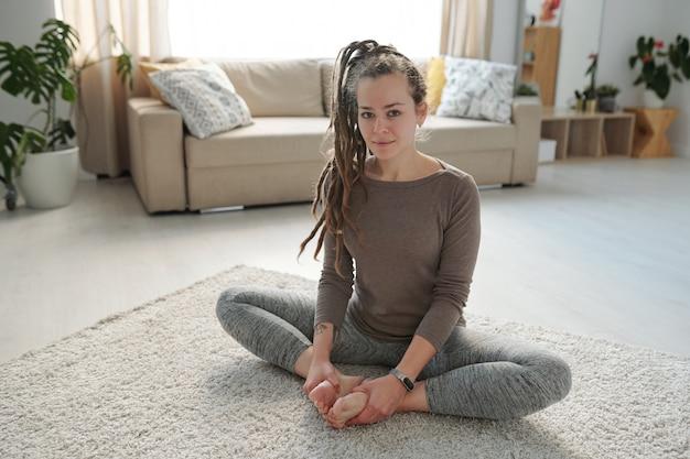 Piuttosto giovane donna attiva mettendo insieme le sue suole nude mentre è seduto sul pavimento durante la pratica dello yoga