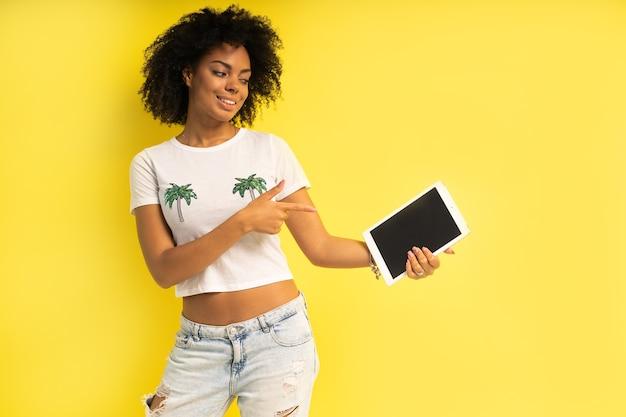 Piuttosto giovane donna afro-americana in piedi e utilizzando computer tablet isolate su sfondo giallo.